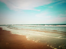 Beach and cloudy sky. Retro style Stock Images