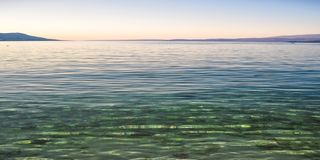 Crystal clear water in the coast of Adriatic Sea island Pag, Croatia after sunset royalty free stock image