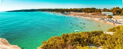 Beach on the coast of Puglia. Beach facilities on bay near rocky cove on the coast of Salento in Puglia in Italy stock images