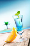 Beach Cocktail. Blue Curacao Beach Cocktail with fresh lemon standing on a landing stage, with the pacific and a lagoon with a palm in the background. More Royalty Free Stock Images