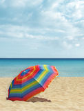 Beach colorful parasol / umbrella. Colorful beach umbrella / parasol in the sand on an empty beach. Vertical shot with copy space Royalty Free Stock Photos