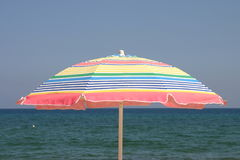At the beach. This colorful beach umbrella in the foreground stood out against the colors of the sky and the ocean Stock Photos