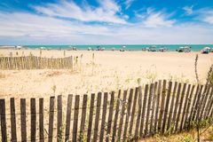Beach with colorful umbrellas, wooden fences and wildlife. Stock Photo