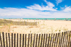 Beach with colorful umbrellas, wooden fences and wildlife. Royalty Free Stock Photos