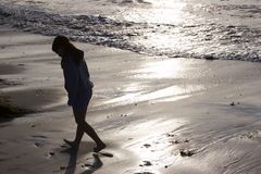 Beach Comber. A girl is silhouetted at the water's edge Stock Photography