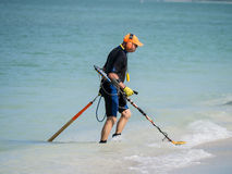 Beach comer with metal detector on the beach Royalty Free Stock Photo