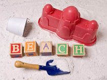 Beach Concept 3. BEACH spelled out in alphabetic blocks and a childs sand toys including a castle, pail and shovel royalty free stock photos