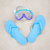 Beach concept - blue flip flops and diving mask on the sand Stock Photo
