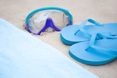 Beach concept - blue flip flops, towel and diving mask on the sa Royalty Free Stock Images