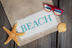 Beach Concept with Sunglasses. A concept for beach vacation with starfish, seashell and red wayfarer  style sunglasses with reflection of sea and sand in lenses Stock Image