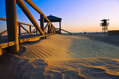 The beach in Conil de la Frontera at sunset. A beach at sunset in a little village in Andalusia called Conil de la Frontera. Lifeguard watchtower in the distance Royalty Free Stock Photography