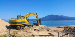 Beach construction after erosion. With excavator on the beach front royalty free stock photography