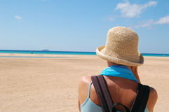 Beach contemplation. Lady wearing a hat and a silk scarf is standing  on a sand beach looking towards ocean. Fuerteventura, Spain Stock Images