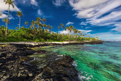 Beach with coral reef and black volcanic rocks on south side of Royalty Free Stock Photography