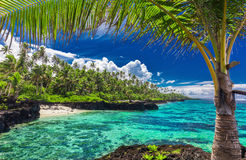 Beach with coral reef on south side of Upolu framed by palm leav Stock Photos