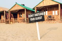 Beach cottage and cabins of sandy resort with sign Dont Disturb Our Guests. Hotel service concept.  Stock Images