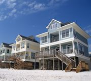 Beach Cottages on a White Sand Coast. Pastel colored beach cottages against a blue sky Royalty Free Stock Photo