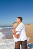 Beach couple. Happy mature couple embracing on a sunny day at the beach Stock Photos