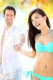 Beach couple. Having fun. Beautiful happy young couple holding hands walking on tropical beach during holidays at beach resort. Interracial couple, Asian women stock image