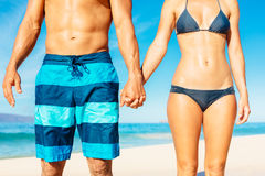 Beach Couple. Attractive Fit Couple on the Beach in Swimwear Holding Hands Royalty Free Stock Photo