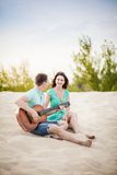 Beach, couple, guitar, sand. The wedding ceremony beautiful bride and groom stylish summer fun smile joy Royalty Free Stock Images