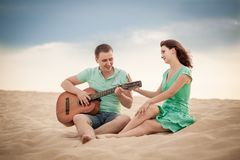 Beach, couple, guitar, sand. The wedding ceremony beautiful bride and groom stylish summer fun smile joy Royalty Free Stock Photos
