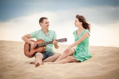 Beach, couple, guitar, sand. The wedding ceremony beautiful bride and groom stylish summer fun smile joy Royalty Free Stock Photography