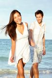 Beach couple happy. Holding hands. Young beautiful couple in love walking on beach at sunset. Asian woman, Caucasian man stock image