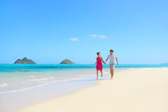 Beach couple happy having fun on Hawaii honeymoon. Romantic couple cheerful and full of happiness on travel vacation on Lanikai beach, Oahu, Hawaii, USA with Royalty Free Stock Photography