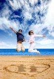 Beach couple having fun - jumping Royalty Free Stock Images