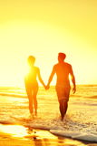 Beach couple holding hands together at sunset Royalty Free Stock Photography