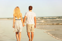 Beach couple holding hands walking at sunset. By ocean sea. Beautiful casual young lovers hand in hand walking away with back at rear view. Summer vacation Stock Photography