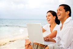 Beach couple on a laptop Royalty Free Stock Photos