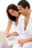 Beach couple on a laptop Stock Photo