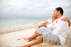 Beach couple on a laptop Stock Photography