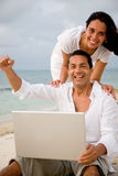 Beach couple on a laptop Stock Image