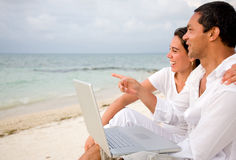 Beach couple on a laptop Royalty Free Stock Images