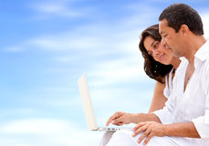 Beach couple on a laptop Stock Images