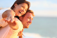 Beach couple laughing in love romance on travel. Honeymoon vacation summer holidays romance. Young happy people, Asian women and Caucasian men embracing Stock Images
