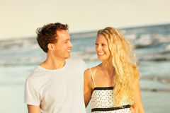 Beach couple laughing walking at romantic sunset. Happy in love. Beautiful young couple enjoying summer vacation honeymoon travel holding hands at ocean sea Royalty Free Stock Photos