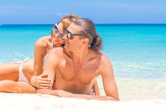 Beach couple looking. Happy young couple lying on sand under sun Stock Photos