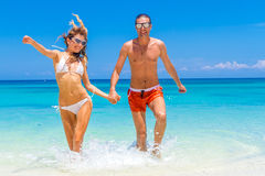 Beach couple looking. Happy young couple lying on sand under sun. Ny summer sun. Travel holidays concept Stock Photography