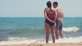 Beach couple looking at ocean view from behind. Couple standing on white sand on vacations and sea waves splashing in. Slow motion. 3840x2160, 4k stock video