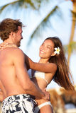 Beach couple in love having vacation summer fun. Holding hands around each other smiling happy on tropical beach on Hawaii. Beautiful young multiracial couple Stock Photo