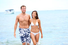 Beach couple in love walking happy in water Royalty Free Stock Photos