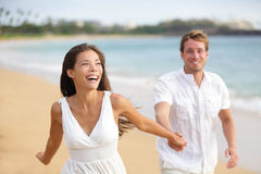 Beach couple running having fun laughing together. During summer travel vacation holiday on beautiful golden beach. Joyful excited multi-ethnic couple, Asian Royalty Free Stock Images