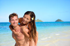 Beach couple vacation fun - happy piggyback. Cute mixed race asian chinese women piggybacking on the back of handsome caucasian men laughing in love during Royalty Free Stock Photography