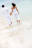 Beach couple walking Stock Photo