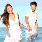 Beach couple walking happy. Carefree and joyful on summer vacation. Interracial young couple holding hands. Asian woman, Caucasian man. From Varadero Beach royalty free stock photo