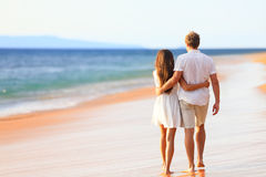 Beach couple walking on romantic travel. Honeymoon vacation summer holidays romance. Back rear view of casual young happy lovers in full body length on beach Stock Photo